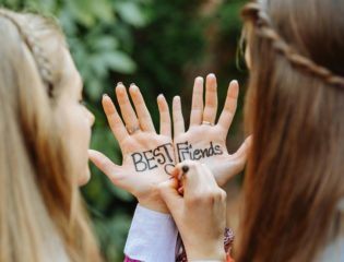 "Two girls writing ""best friends"" on their hands"
