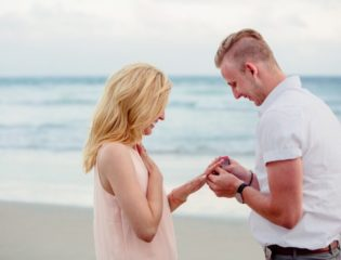 Man asking a woman to marry him at the beach