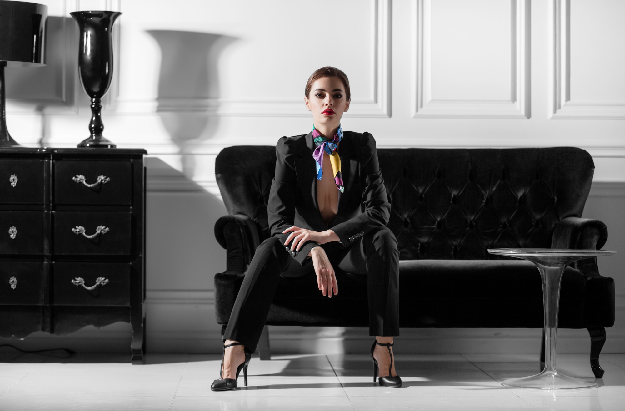 Woman sitting in a sofa wearing a stylish outfit in black