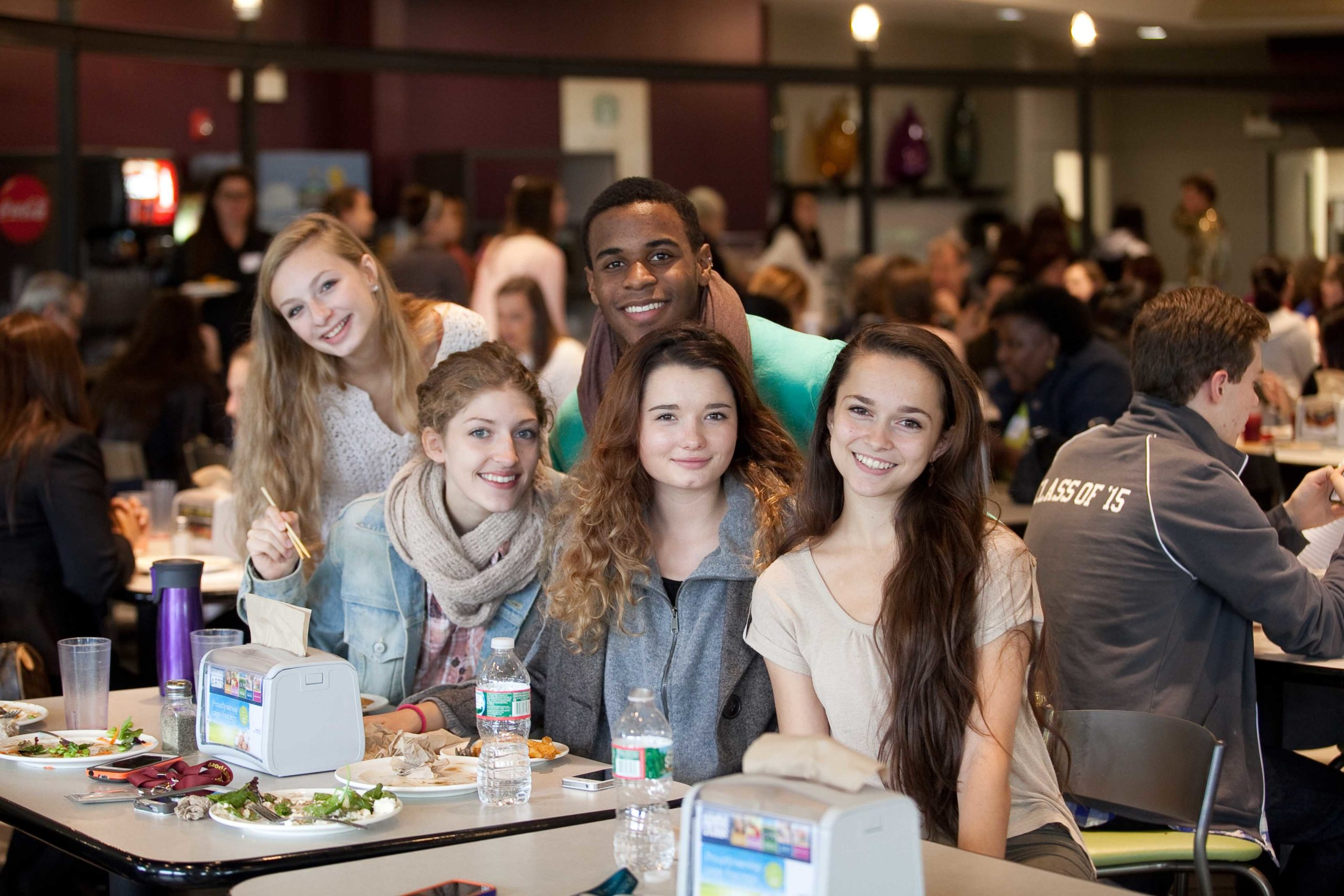 Young people posing for a picture in a cafeteria