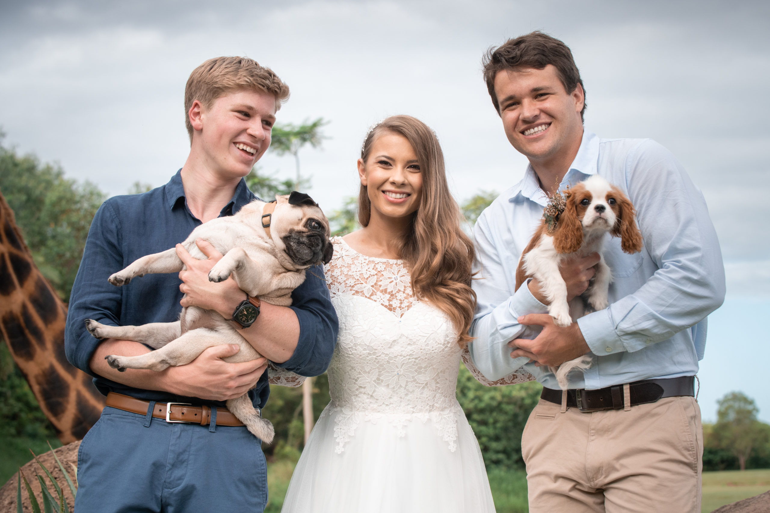Chandler Powell and Bindi Irwin and Robert Iwin. Chandler is holding 'piggy' and Robert is holding 'Stella'