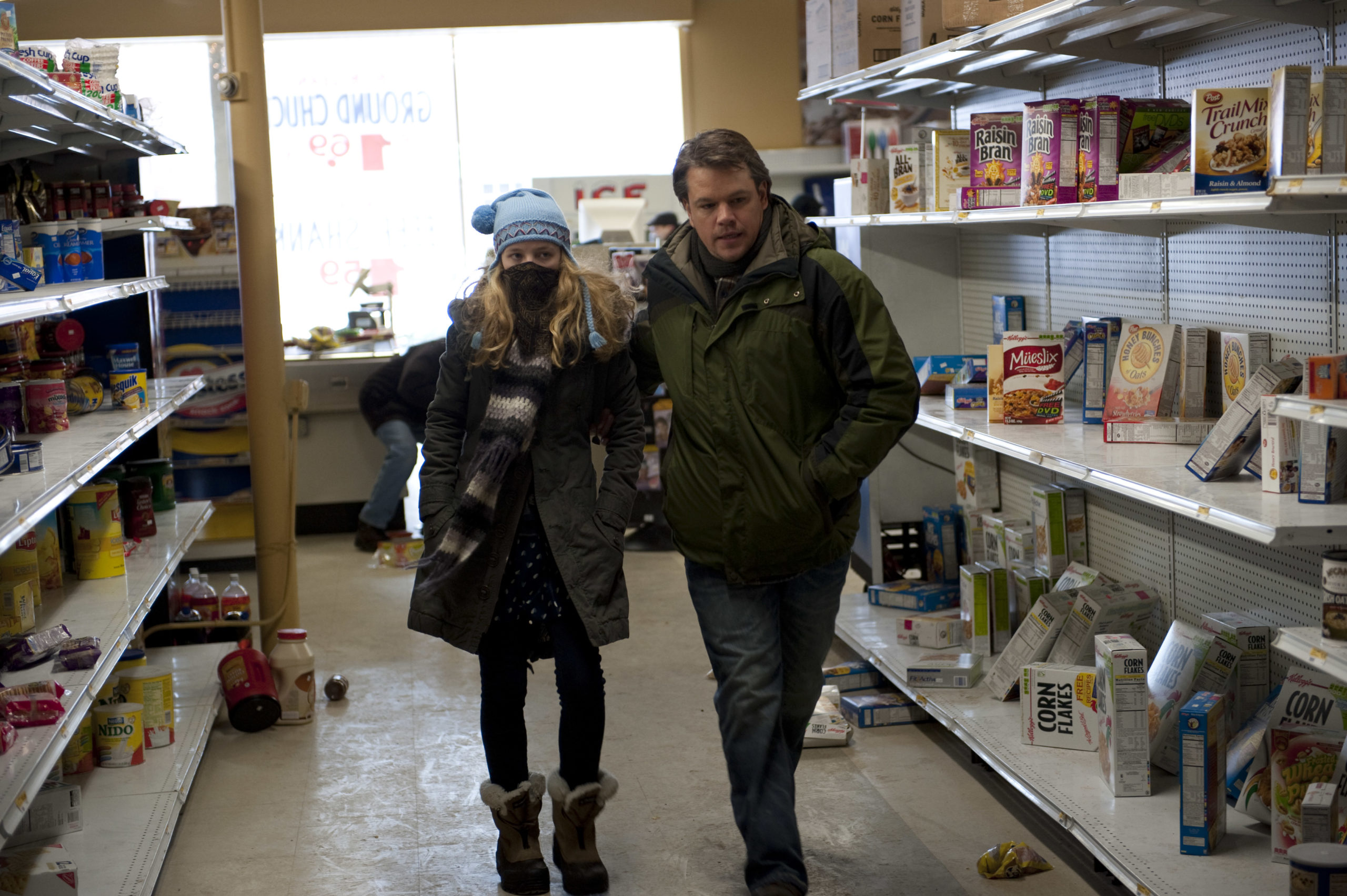 Scene from the movie Contagion; man and woman walking along the isles of a half-empty store