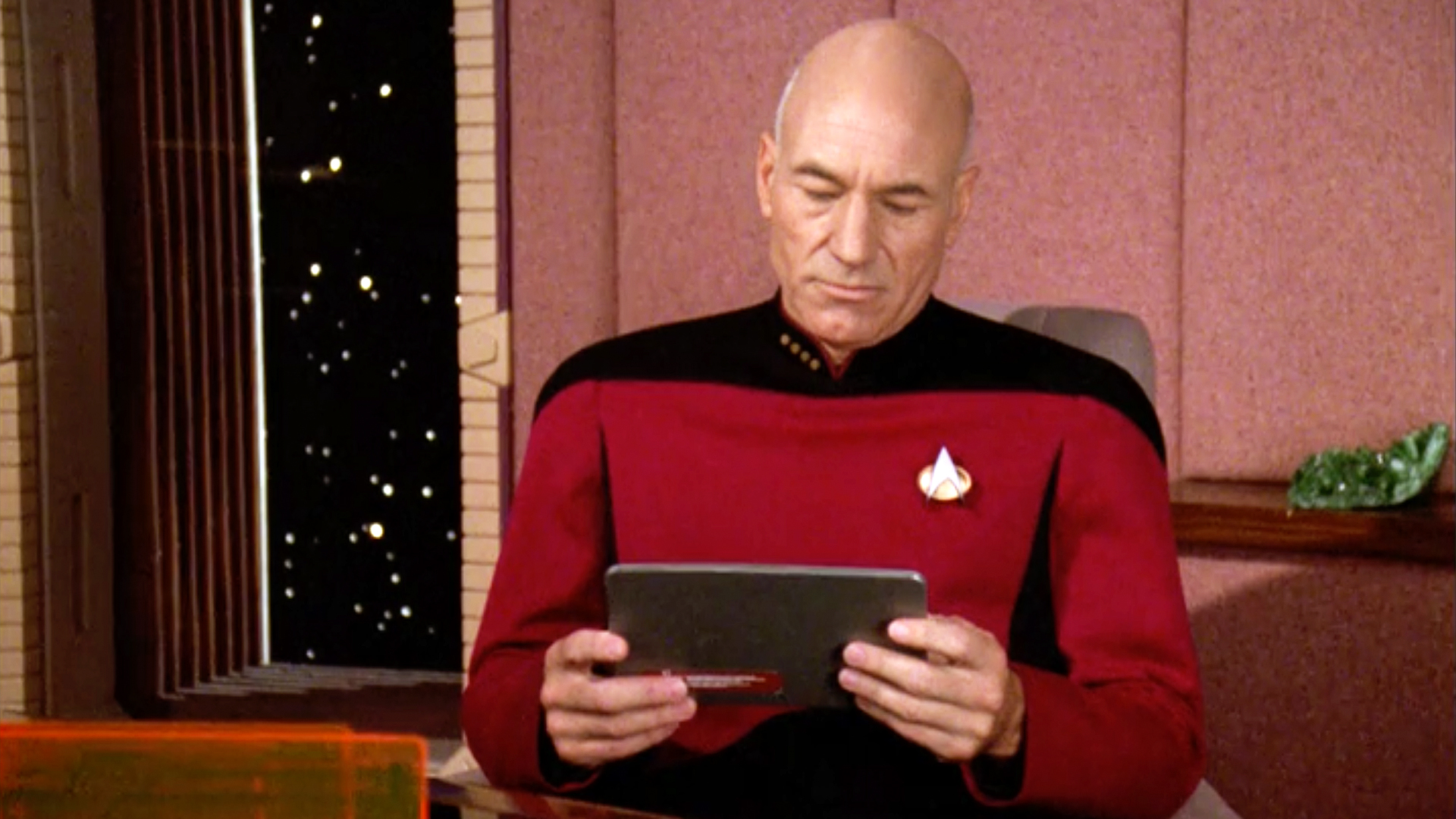 Captain Picard holding a PADD