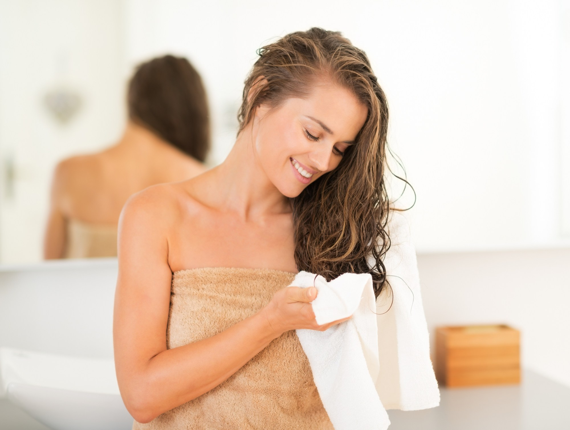 Woman after bath taking care of her hair with a white towel