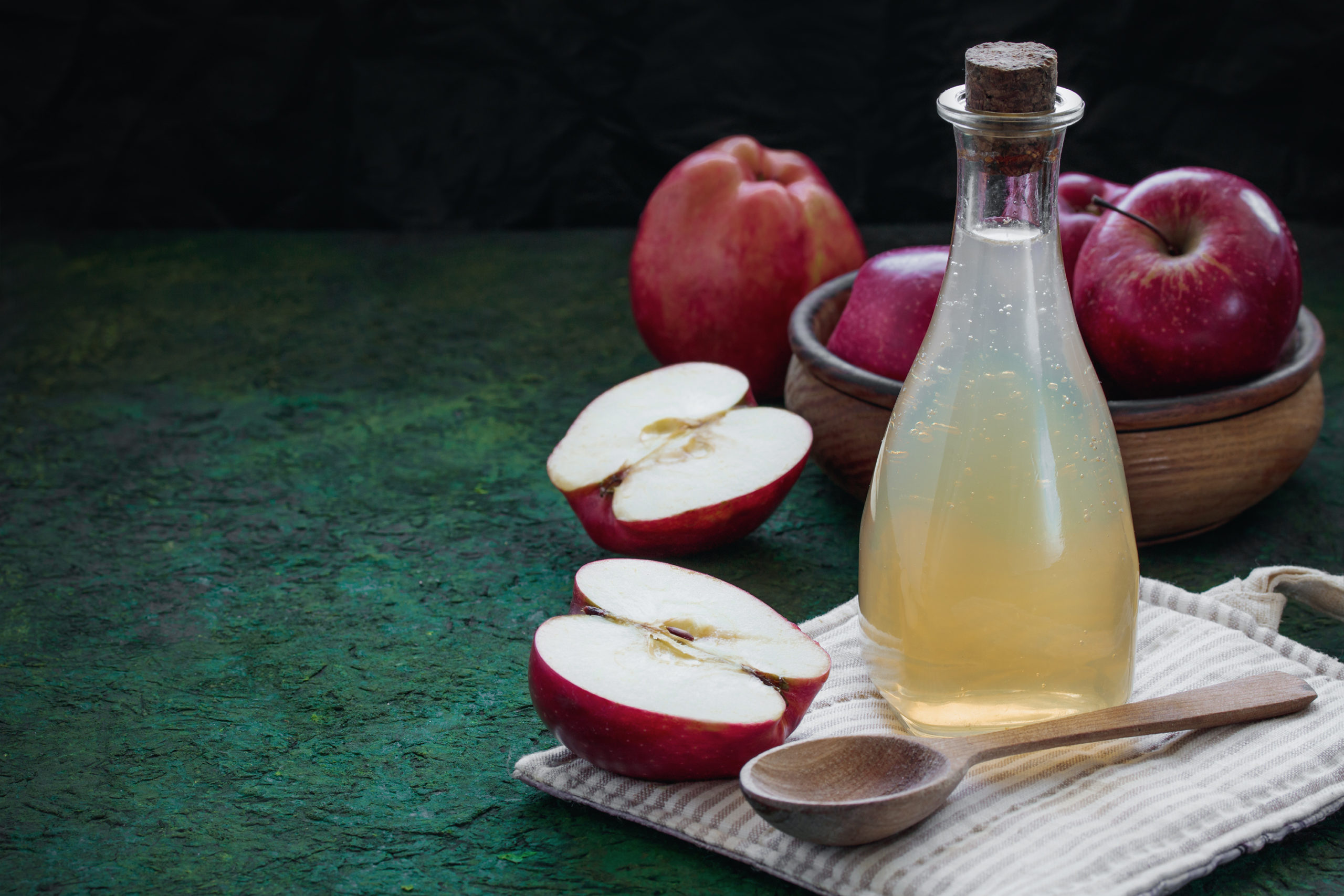 Glass bottle with apple cider vinegar, whole fresh red apples on a green black background