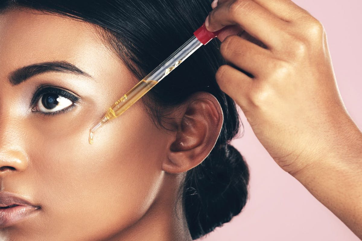 woman applying jojoba oil on her face