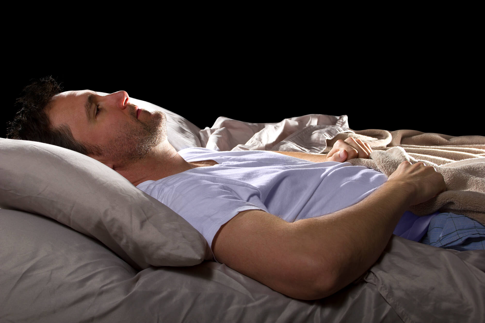 Man laying in bed, looking worried