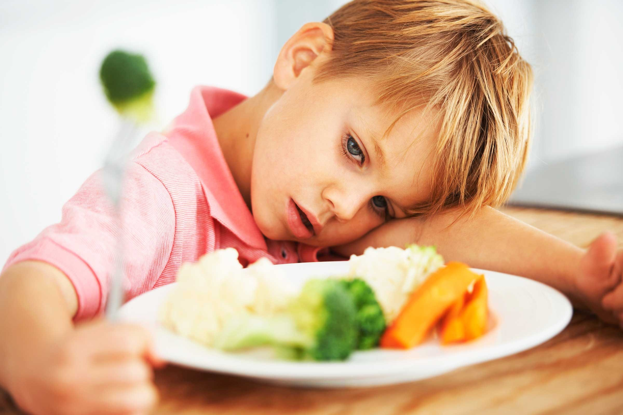 Young boy looking disinterested in the food on his plate