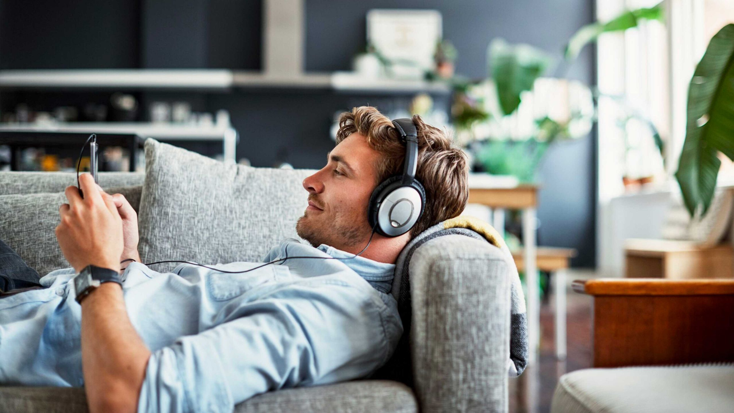 Man laying in bed with his headphones on, listening to podcasts