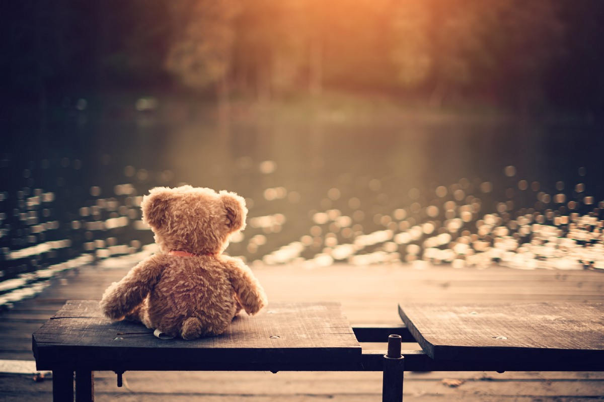 Lonely teddy bear left on a bench